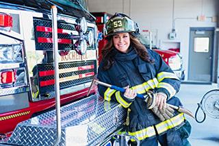 Lori Becker in her firefighting gear, leaning against a fire truck.